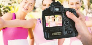 Composite image of cropped hand of photographer holding camera. Cropped hand of photographer holding camera  against portrait of happy young female athletes Stock Photos
