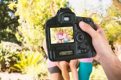 Composite image of cropped hand of photographer holding camera. Cropped hand of photographer holding camera against young athlete women cheering after victory Royalty Free Stock Images