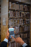 Composite image of cropped hands of businessman using calculator Royalty Free Stock Photography