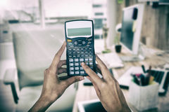 Composite image of cropped hands of businesswoman using calculator Royalty Free Stock Photography