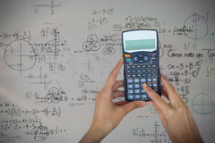 Composite image of cropped hands of businesswoman using calculator Stock Images