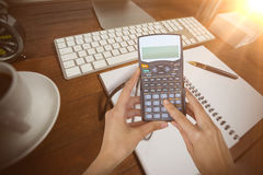 Composite image of cropped hands of businesswoman using calculator Royalty Free Stock Images