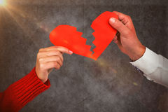 Composite image of cropped hands of couple holding cracked red heart shape Stock Photography