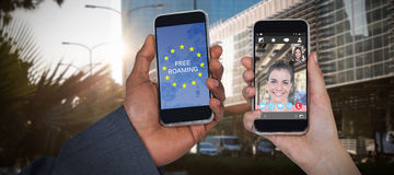 Composite image of cropped hands of man and woman holding mobile phones. Cropped hands of men and women holding mobile phones against front side of buildings Stock Photography