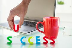 Composite image of cropped image of businessman arranging success word. Cropped image of businessman arranging success word against laptop on desk with red mug Royalty Free Stock Image