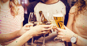 Composite image of cropped image of friends toasting with beer and wine. Cropped image of friends toasting with beer and wine against flying colours Stock Photography