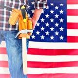 Composite image of cropped image of handyman wearing tool belt Stock Image