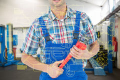 Composite image of cropped image of plumber holding monkey wrench. Cropped image of plumber holding monkey wrench against empty work stations royalty free stock photo