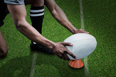 Composite image of cropped image of sportsman keeping rugby ball on kicking tee Royalty Free Stock Images