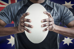 Composite image of cropped image of sportsman pressing rugby ball Royalty Free Stock Photo