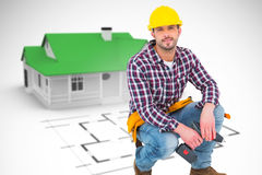 Composite image of crouching handyman holding power drill. Crouching handyman holding power drill against blue house behind an architectural plan Royalty Free Stock Photo