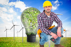 Composite image of crouching handyman holding power drill. Crouching handyman holding power drill against wind turbines and bulb full of leaves Stock Images
