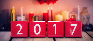 Composite image of cubes with numbers. Cubes with numbers against candles and christmas decorations arranged on fireplace Stock Photography