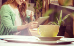 Composite image of cup of coffee and tablet pc. Cup of coffee and tablet pc against smiling woman drinking coffee and using tablet Stock Image