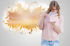 Composite image of curious young woman holding a gift while opening it Royalty Free Stock Photo