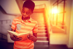 Composite image of cute boy reading book in library Stock Photography