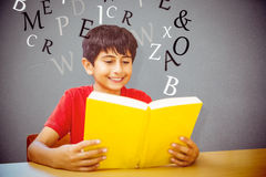 Composite image of cute boy reading book in library Stock Photo