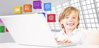 Composite image of cute boy using laptop Stock Image