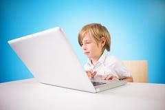 Composite image of cute boy using laptop Stock Photos