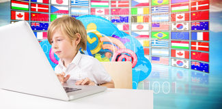 Composite image of cute boy using laptop Stock Photography