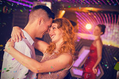 Composite image of cute couple dancing together on dance floor Royalty Free Stock Photography