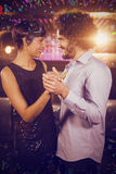 Composite image of cute couple dancing together on dance floor stock images