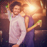 Composite image of cute couple dancing together on dance floor while having drink stock photo