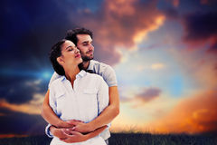 Composite image of cute couple embracing with eyes closed Stock Photography
