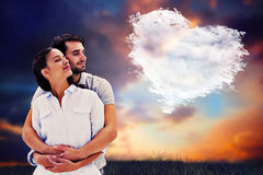 Composite image of cute couple embracing with eyes closed Stock Photos