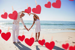 Composite image of cute couple forming heart shape with arms Stock Photos