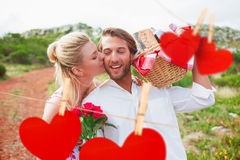 Composite image of cute couple going for a picnic with woman kissing boyfriends cheek Stock Images