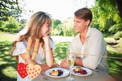 Composite image of cute couple having champagne and desert in the park Royalty Free Stock Photography