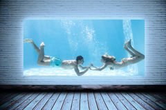 Composite image of cute couple holding hands underwater in the swimming pool Royalty Free Stock Photos