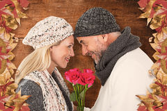 Composite image of cute couple holding rose while looking at each other Stock Images