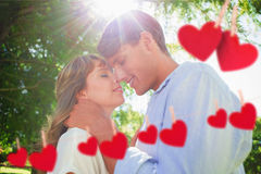 Composite image of cute couple hugging and smiling in the park Royalty Free Stock Photos