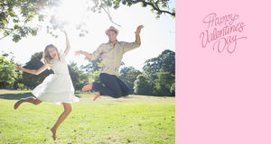 Composite image of cute couple jumping in the park together Royalty Free Stock Image