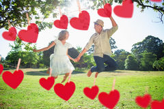 Composite image of cute couple jumping in the park together holding hands Stock Images