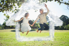 Composite image of cute couple jumping in the park together holding hands Royalty Free Stock Photo