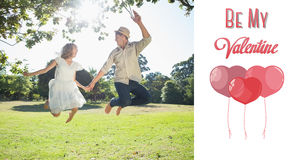 Composite image of cute couple jumping in the park together holding hands. Cute couple jumping in the park together holding hands against cute valentines message Royalty Free Stock Images