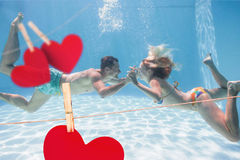 Composite image of cute couple kissing underwater in the swimming pool Royalty Free Stock Photo