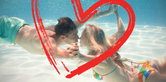 Composite image of cute couple kissing underwater in the swimming pool Stock Photo