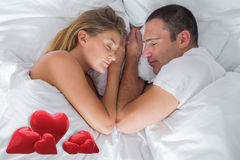 Composite image of cute couple lying asleep in bed Royalty Free Stock Images