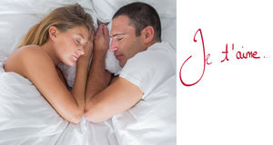 Composite image of cute couple lying asleep in bed Royalty Free Stock Photography