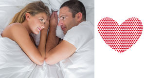 Composite image of cute couple lying and looking at each other in bed Stock Photos
