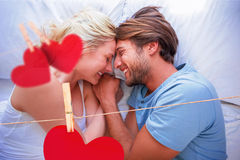 Composite image of cute couple relaxing on bed smiling at each other Royalty Free Stock Photo