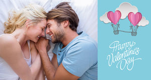 Composite image of cute couple relaxing on bed smiling at each other. Cute couple relaxing on bed smiling at each other against cute valentines message Stock Images
