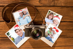 Composite image of cute couple in santa hats shopping online with laptop. Cute couple in santa hats shopping online with laptop against instant photos on wooden Stock Image