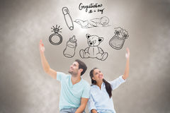 Composite image of cute couple sitting with arms raised Royalty Free Stock Image