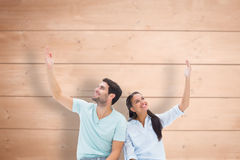 Composite image of cute couple sitting with arms raised Stock Image