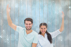 Composite image of cute couple sitting with arms raised Royalty Free Stock Photo